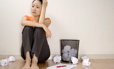 stressed woman next to crumbled paper