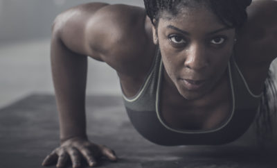 Black woman doing push-ups in dark gym