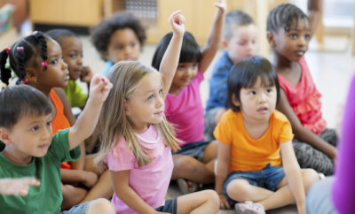 Preschool children raising hands