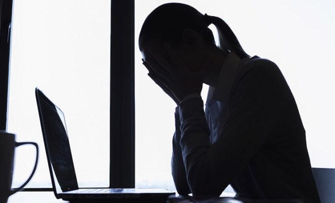 woman bowed at desk